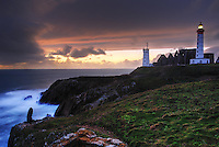 Sunset on the lighthouse of Pointe Saint-Mathieu and the old Menhir, Finistere, Bretagne, Brittany, France