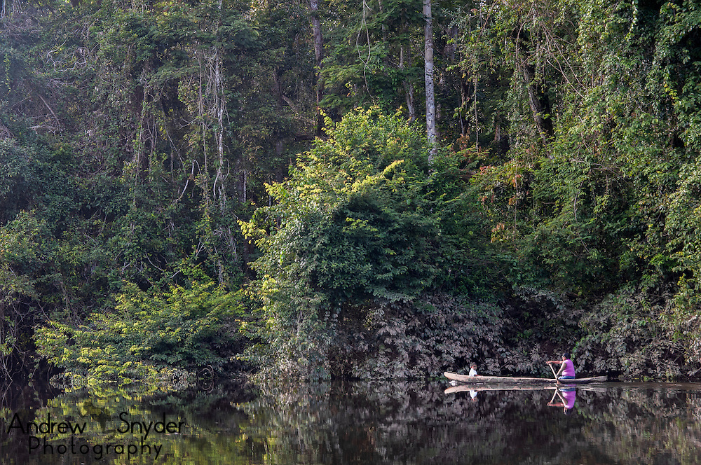 An Amerindian woman takes her child home from school by canoe. Potaro River, Guyana.