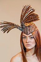 Portrait of a young woman wearing feathered headdress on colored background