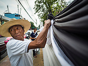 18 OCTOBER 2016 - BANGKOK, THAILAND:  Workers at Wat Bowon Niwet, a Buddhist temple affiliated with the Thai monarchy, hang black and white mourning bunting on the wall around the temple in honor of the late Bhumibol Adulyadej, the King of Thailand. The King died Oct. 13, 2016. He was 88. His death came after a period of failing health. Bhumibol Adulyadej was born in Cambridge, MA, on 5 December 1927. He was the ninth monarch of Thailand from the Chakri Dynasty and is also known as Rama IX. He became King on June 9, 1946 and served as King of Thailand for 70 years, 126 days. He was, at the time of his death, the world's longest-serving head of state and the longest-reigning monarch in Thai history.    PHOTO BY JACK KURTZ