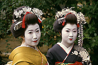 Two geishas pause briefly for a rare portrait between jobs.
