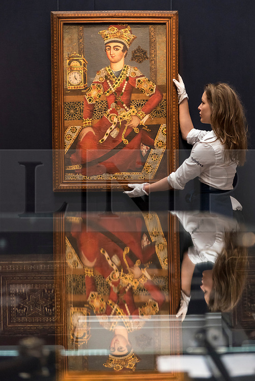 """© Licensed to London News Pictures. 20/04/2018. LONDON, UK. A technician presents """"A portrait of Khosrow Parviz, Circle of Mihr Ali, Persia, Qajar"""", dated 1217, (Est. GBP25-35k) at a preview of works in Sotheby's 20th Century Middle East, Orientalist and Islamic upcoming art sales in New Bond Street.  The works will be sold at auction in the last week of April.    Photo credit: Stephen Chung/LNP"""