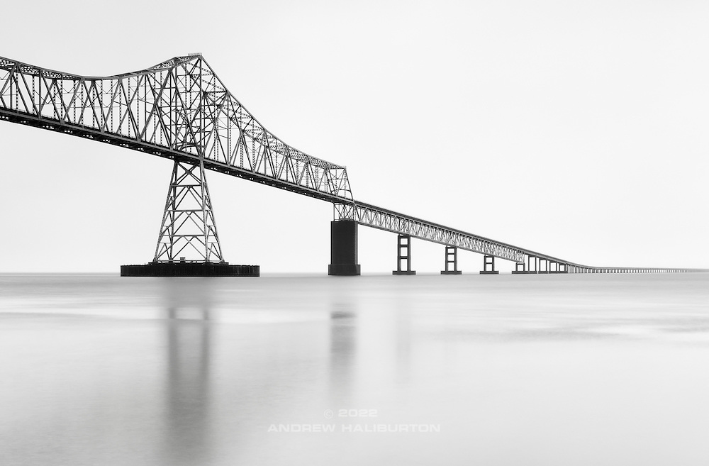 "This image, ""Ebb Tide, Columbia River, Astoria"" was previsualized.  But what wasn't anticipated was the constant rain.  Working in the pre-dawn darkness, I had to hold an umbrella with one hand while setting up tripod and camera with the other.  The Astoria-Megler Bridge (4.1 mi / 6.5km long) spans the mouth of the Columbia River between Astoria, Oregon and Point Ellice near Megler, Washington. Construction was started in 1962 and completed in 1966."