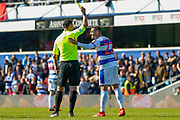 Referee Andrew Madley gives Queens Park Rangers defender Angel Rangel (22) a yellow card during the EFL Sky Bet Championship match between Queens Park Rangers and Swansea City at the Loftus Road Stadium, London, England on 13 April 2019.