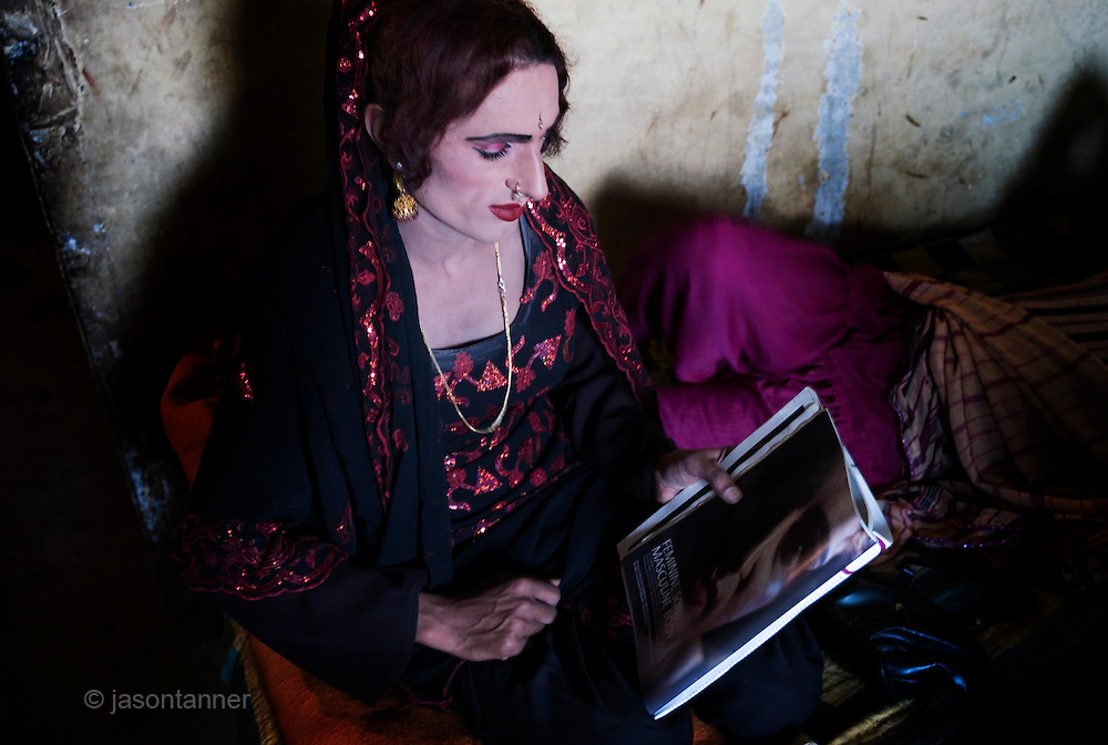 Reema, a 35 year old Hijra  reads an article which features a portrait of her in a local Mens Magazine before leaving for the evenings work on the streets of Karachi...The word Hijra is an Urdu word meaning eunuch or hermaphrodite. However, most Hijras in Pakistan are gay men who leave home to join the Hijra community as young boys where there is more acceptance. Most identify themselves as more feminine then masculine and dress and act accordingly...Although tolerated in a country where homosexuality is against the law, Hijras are largely ostracised from society. They are often denied work opportunities, rejected by most families, lack formal education and live in poorer areas of the city...They share similarities with the more famous Hijra communities in the Indian subcontinent and Bangladesh. In a continent where great emphasis is placed on one's ability to have children, those who are unfortunate not to be able to conceive children are not considered a true man or woman. Life for many Hijras in Pakistan consists of begging for alms (Zakat) in the more prosperous areas of the city as well as slums in addition to receiving alms when bestowing blessings on male babies and at weddings....Most Hijras dress as women, and engage in activities such as dancing and entertaining in public - activities that would be considered inappropriate for women of the subcontinent. Some members of the community engage in prostitution. .