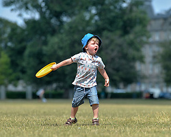Pictured: 3 year old Elliott Brennan from Leith has fun in the sun playing frisbee on Leith Links as the Capital sweltered in 27 degree heat.<br /> <br /> © Dave Johnston / EEm