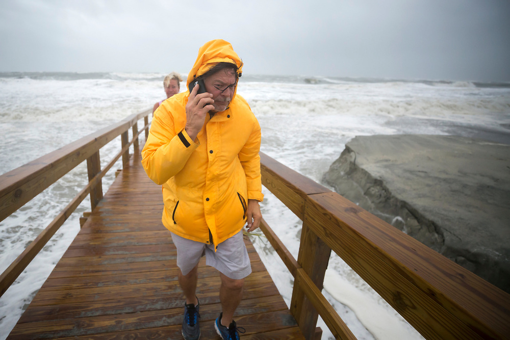 Chip Clayton makes a call to a family member from a beach cross over during Tropical Depression Irma, Monday, Sept., 11, 2017 on Tybee Island, Ga. (AP Photo/Stephen B. Morton)