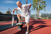 Senior male tennis player with back pain on court