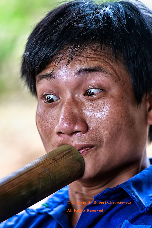 Beady Eyes: A man displays a beady eyed, comical look, as he puts all his effort into drawing upon his hookah, Mai Chau Vietnam.