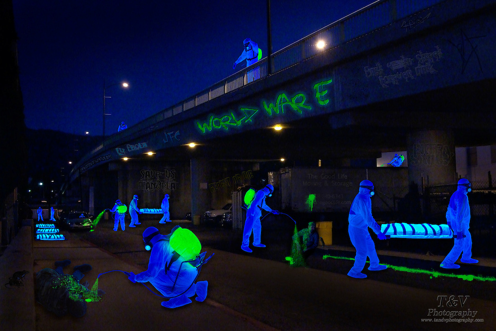Night time street scene of Hazmat uniformed men collecting bodies and spraying infected corpses.Black light