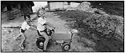 Farmerboys playing with plastic tractor; zwei Bauernbuben spielen mit einem Plastik-traktor, garçons de paysans s'amusent à l'alpage avec un tracteur en plastic