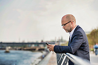 Portrait of mature businessman leaning on railing while using smartphone