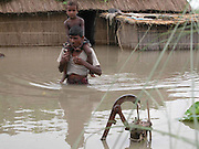 CAPTION : THIS VILLAGE MAN IS TRYING REACH A SAFER PLACE WITH HIS NEPHEW OF  VAGUAMARI VILLAGE SOME 325 KILOMETERS OF  GUWAHATI, THE CAPITAL OF NORTHEASTERN INDIAN STATE OF ASSAM, 04TH JULY, 2003. RIVERS SWOLLEN BY INCESSANT   MONSOON RAINS OVERFLOWING WATERS, WHICH CROSS THE DANGER LAVEL AND BREAK THE DAMS, DYKES AND BANKS, POURING WATER INTO THE HOMES OF ABOUT 800,000 PEOPLE AND SEVERING TRANSPORTATION LINKS IN NORTHEASTERN INDIA, WHILE MORE THAN THOUSANDS VILLAGES SPREAD OVER 10 DISTRICTS IN THE STATE HAVE BEEN WORSTLY AFFECTED BY THE FLOODS AND THE WATER-BORNE DISEASES LIKE GASTROENTERITIS, DYSENTERY, JAUNDICE AND TYPHOID HIT THE FLOOD-AFFECTED AREAS, WHICH TOOK THE SEVERAL LIVES, OFFICIALS OF  THE FLOOD CONTROL, GOVERNMENT OF ASSAM (INDIA) DEPARTMENT DISCLOSED. (PIC - SHIB SHANKAR CHATTERJEE/AP)