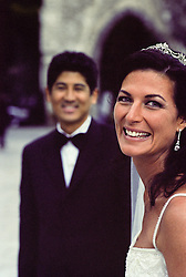 Bride smiling in foreground and groom in the background also smiling