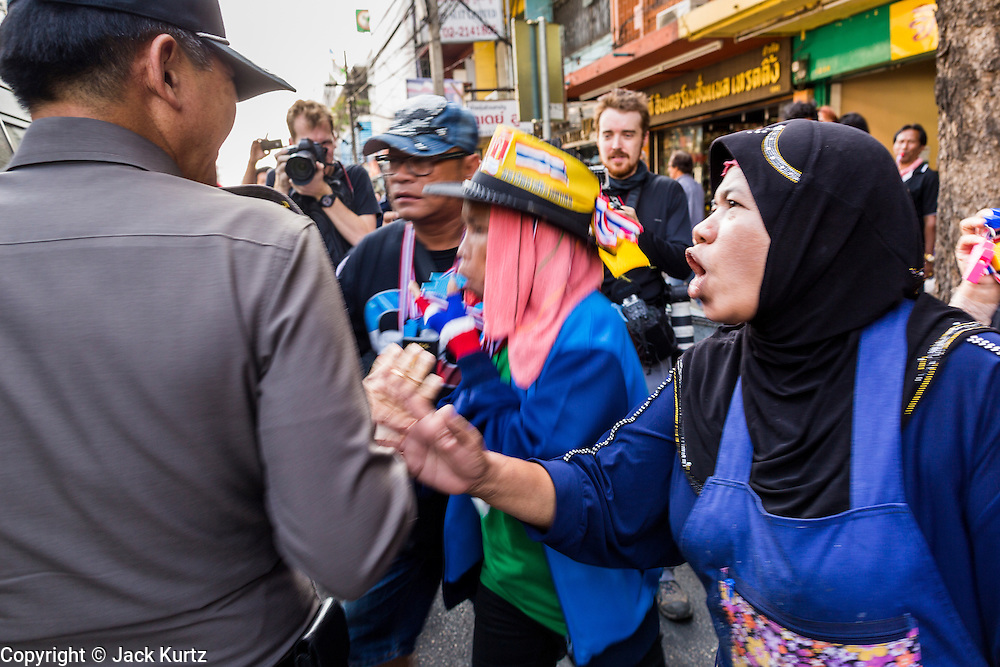 17 JANUARY 2014 - BANGKOK, THAILAND: Anti-government protestors taunt Thai police officers investigating the scene of an IED attack on protestors Friday. Protestors believe the police are allied with government. The attackers were not found but officials claim to have found a weapons cache in an abandoned building nearby. Friday was day 5 of the anti-government Shutdown Bangkok protests. The protest, led by the People's Democratic Reform Committee, is calling for the suspension of elections pending political reform in Thailand. There was violence at several sites in Bangkok Friday, including running battles between government opponents and supporters at one site and an IED attack by unknown assailants on anti-government protestors at another site.    PHOTO BY JACK KURTZ