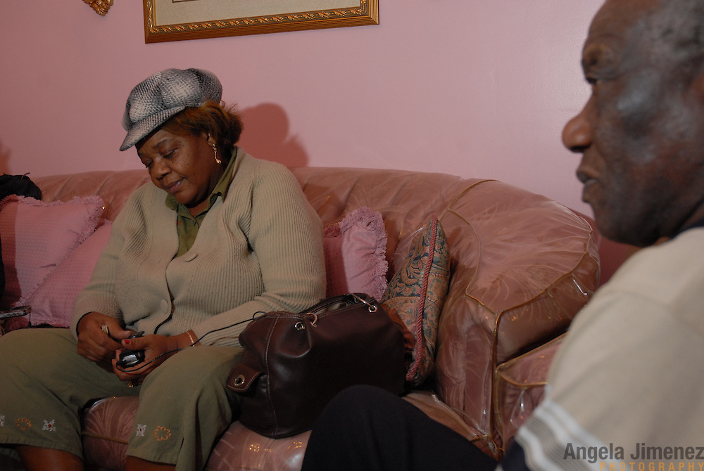 DATE: 11/30/06<br /> DESK: METRO<br /> SLUG: DORISMOND<br /> ASSIGN ID: 30034202A<br /> <br /> Marie Rose Dorismond, left, whose son, Patrick, 26, was killed by undercover New York City Police narcotics detective Anthony Vasquez during a drug buy-and-bust operation on March 16, 2000 sits in the home of family member Verdieu Castelly, right (he is her half-brother and raised her as a father) on New York Avenue near Avenue D in East Flatbush, Brooklyn after a 27-hour Greyhound bus ride from her home in Port St. Lucie, Florida on November 30, 2006. She has come back to the city to attend the funeral of Sean Bell, 23, who was killed last week by New York City police officers. Vasquez was acquitted of all charges related to the killing of Dorismond's son. <br /> <br /> photo by Angela Jimenez for The New York Times<br /> photographer contact 917-586-0916