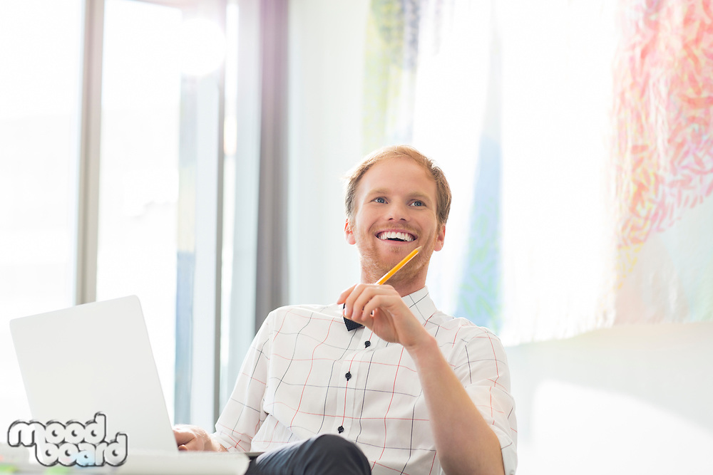 Happy businessman looking away while sitting at desk in creative office