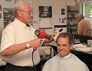 Ralph Williams (left) cuts the hair of long-time customer Gary Wilson, from Middletown as Don Stoneking (right) looks on at Scotty's Barber Shop, Wednesday, June 27th.  Wilson was Williams' first customer 46 years ago.