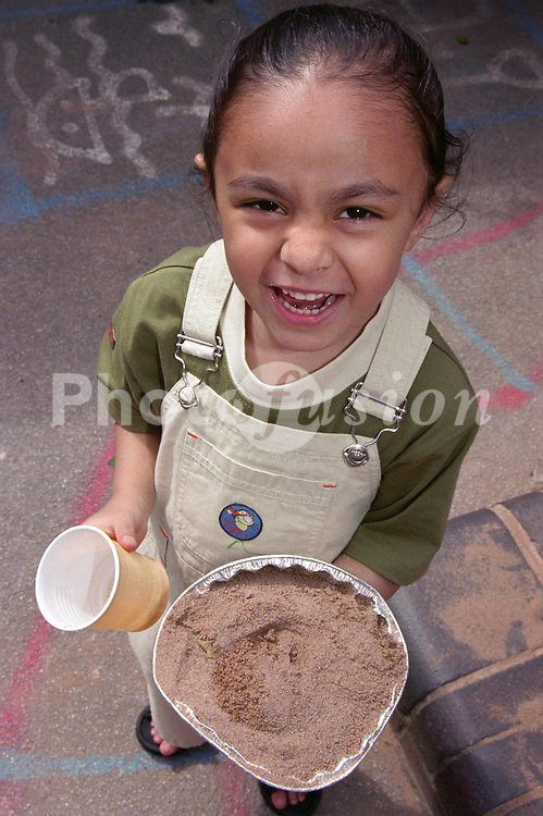 Nursery school girl standing in playground holding foil container filled with sand,