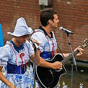 NLD/Amsterdam/20100807 - Boten tijdens de Canal Parade 2010 door de Amsterdamse grachten. De jaarlijkse boottocht sluit traditiegetrouw de Gay Pride af. Thema van de botenparade was dit jaar Celebrate, BNN boot, nick & Simon in Delfts blauwe jurk