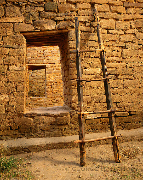 0210-1001B ~ Copyright: George H. H. Huey ~ Prehistoric ladder, uncovered by archeologist Earl Morris, and doorways of the West Pueblo Ruin, @ A.D. 1100. Aztec Ruins National Monument, New Mexico.