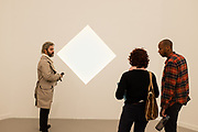 """New York, NY - May 3, 2019. Spectators with James Turrell's etched glass and LED """"Praamzius"""" in the Kayne Griffin Corcoran Gallery at the Frieze Art Fair on New York City's Randalls Island."""