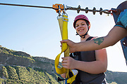 Woman smiles while zip lining in the Snake River Canyon with Zip the Snake in Twin Falls, Idaho.