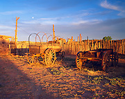 0108-1003B ~ Copyright: George H. H. Huey ~ Historic commercial wagons in corall behind trading post at sunset with moon rising. [Trading post built in remote corner of Navajo Indian Reservation 1878, and still active today]. Hubbell Trading Post National Historic Site, Arizona.