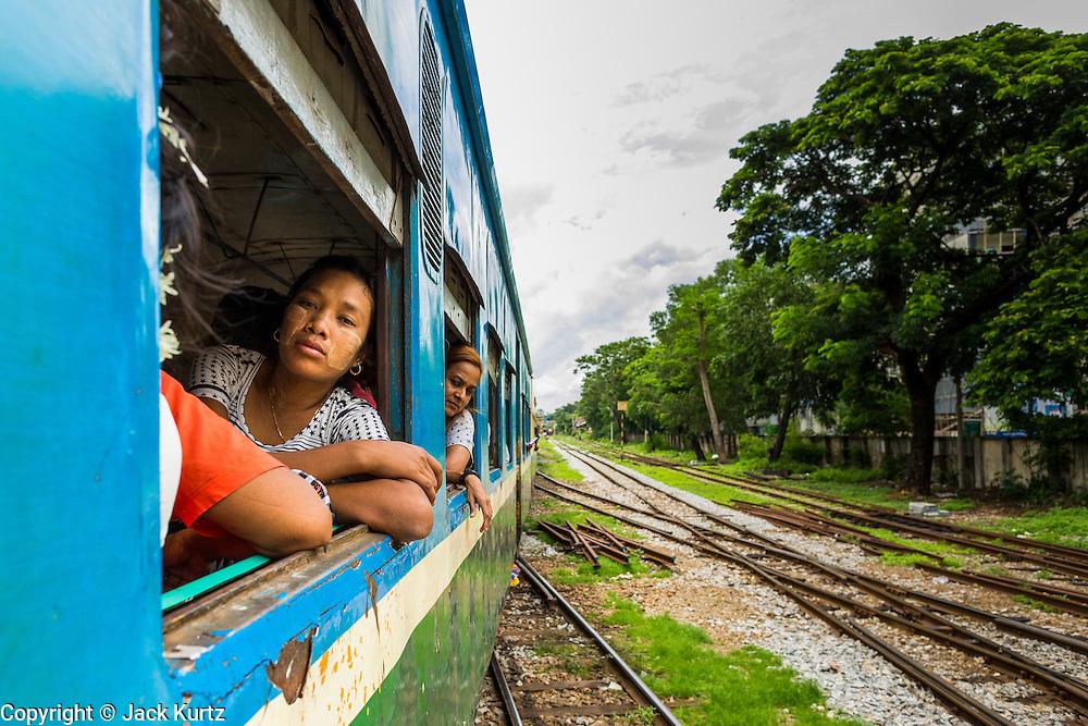 05 JUNE 2014 - YANGON, YANGON REGION, MYANMAR: Passengers on the Yangon Circular Train. The Yangon Circular Train is a commuter train that circles Yangon, Myanmar (Rangoon, Burma). The train is 45 kilometers long, makes 38 stops and takes about three hours to make a loop of the city.     PHOTO BY JACK KURTZ