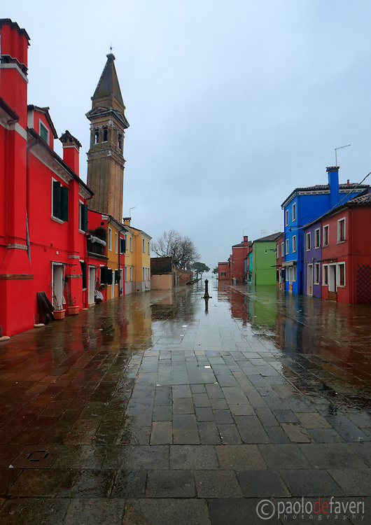 A calle (street) in the small island of Burano, in the Venetian lagoon and part of the city of Venice, Italy. The tilted campanile (bell tower) of the parish church of Burano is in the background