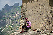 LIANGSHAN, CHINA - MAY 14: (CHINA OUT) <br /> <br />  A girl sits on stone in Atuler village located at the 800-meter-high cliff on May 13, 2016 in Liangshan Yi Autonomous Prefecture, Sichuan Province of China. 72 families lived in Atuler village on the 800-meter cliff at Meigu River Canyon in Liangshan Yi Autonomous Prefecture. 15 pupils, aged 6 to 15, accompanied by 3 adults regularly spent 2 hours climbing 17 vines ladders hung on the 800-meter-high cliff to go between school and home twice a month. Villagers used the same ladders to go to the nearest market once a week to sell peppers and walnuts and buy necessities.<br /> ©Exclusivepix Media