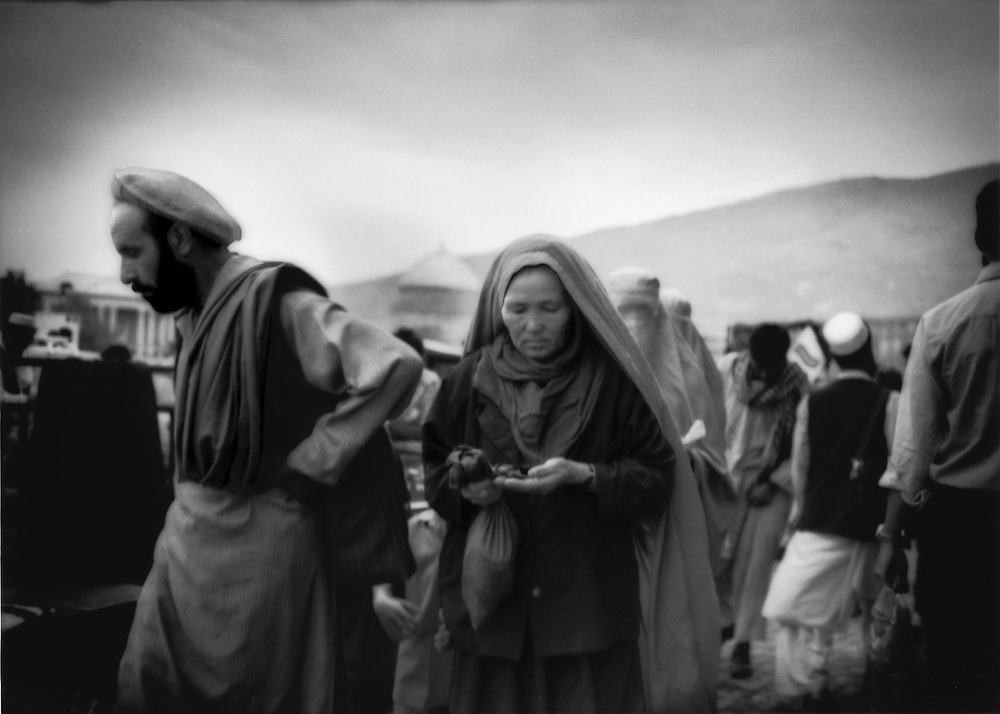 Woman has pulled back her burkha, revealing her face, so that she can count her change in the bazaar beside the Kabul River, Afghanistan.