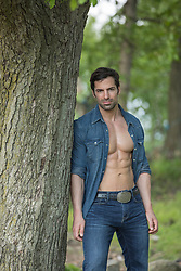 hot man in an open denim shirt by a tree
