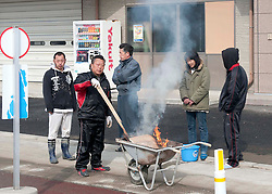 London News Pictures. 20/03/2011. Workers trying to clean debris in Onagawa, Japan, keep themselves warm with a fire in a wheelbarrow made from dried flotsam.  Thousands are missing after a 9.0 magnitude strong earthquake struck on March 11 off the coast of Japan causing a tsunami wave. Photo credit should read Alex Tee/London News Pictures.