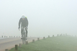 © Licensed to London News Pictures. 13/03/2014. Richmond, UK . A man cycles through the park. Deer graze and feed in the heavy fog at Richmond Park, Surrey, today 13th March 2014. Photo credit : Stephen Simpson/LNP