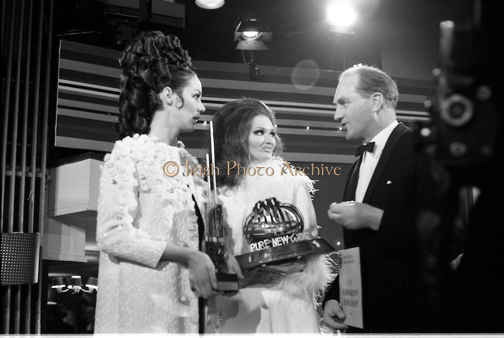 07/01/1969.01/07/1969.07 January 1969.Eurofashion Final at Shelbourne Hotel. The Irish section of the 1969 Eurofashion Contest judged by John McGuire, Miss Leonora Currie and Mrs Nuala Mc Laughlin. Pictured are winner Colette Dowling (21) Kincora Road, Clontarf,(centre) and model Liz Willoughby, wearing one of Miss Dowling's winning outfits, being presented with 1st prize by George Collley, Minister for Industry and Commerce. the trophy was designed byPatrick MacMahon.