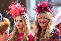 © Licensed to London News Pictures. 08/04/2016. Liverpool, UK. Two glamorous women wear brightly coloured hats on Ladies Day at the Grand National 2016 at Aintree Racecourse near Liverpool. The race, which was first run in 1839, is the most valuable jump race in Europe. Photo credit : Ian Hinchliffe/LNP