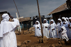 Members of the Legion Maria Church pray. Mathare, one of the poorest slums in Nairobi.  Running water and electricity are scarce and trash and human waste fills the streets.  Many people have no jobs and those who do work can earn less than one dollar a day.