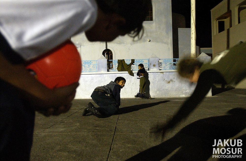 Children play in front of a Greek Orthodox Church in the town of Ia on the island of Santorini, Greece on October 14, 2002. Photo by Jakub Mosur