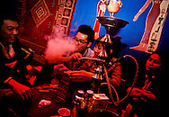 A young Vietnamese man smokes a shisha at Dragonfly Bar in Hanoi, Vietnam