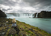 Young woman sitting by Goðafoss
