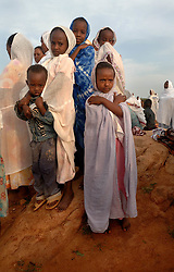 "Coptic christians pray outside St. Mary's church in the village of Fithi which means ""justice"" on the outskirts of  Barentu, Eritrea August 27, 2006. During this ceremony, Tiblits neighbor Zaid Tesheme, 31 had her baby baptized with the name Mihreteab. The donkey that Tiblets received from the womens union ""Hamade"", helped them prepare for the celebration afterwards.   (Photo by Ami Vitale)"