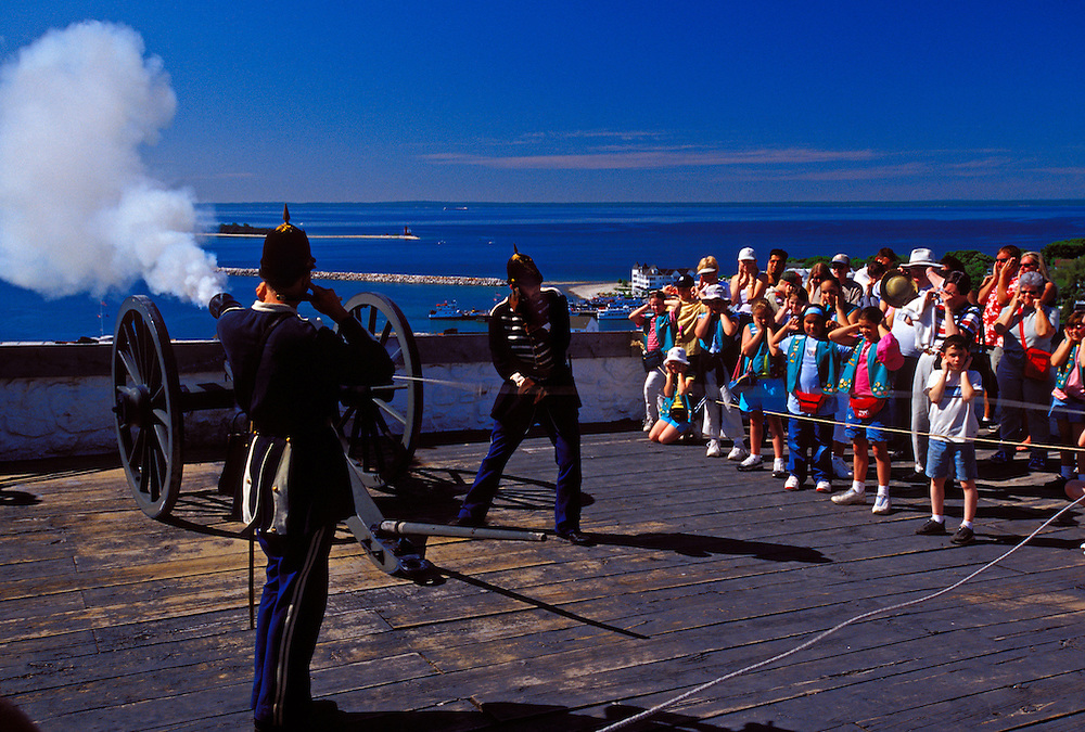 TOURISTS COVER THEIR EARS AS SOLDIERS AT FORT MACKINAC ON MACKINAC ISLAND, MICHIGAN FIRE A CANON.