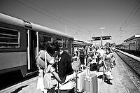 passeggeri in attesa sulla banchina della stazione. Reportage che analizza le situazioni che si incontrano durante un viaggio lungo le linee ferroviarie delle Ferrovie Sud Est nel Salento