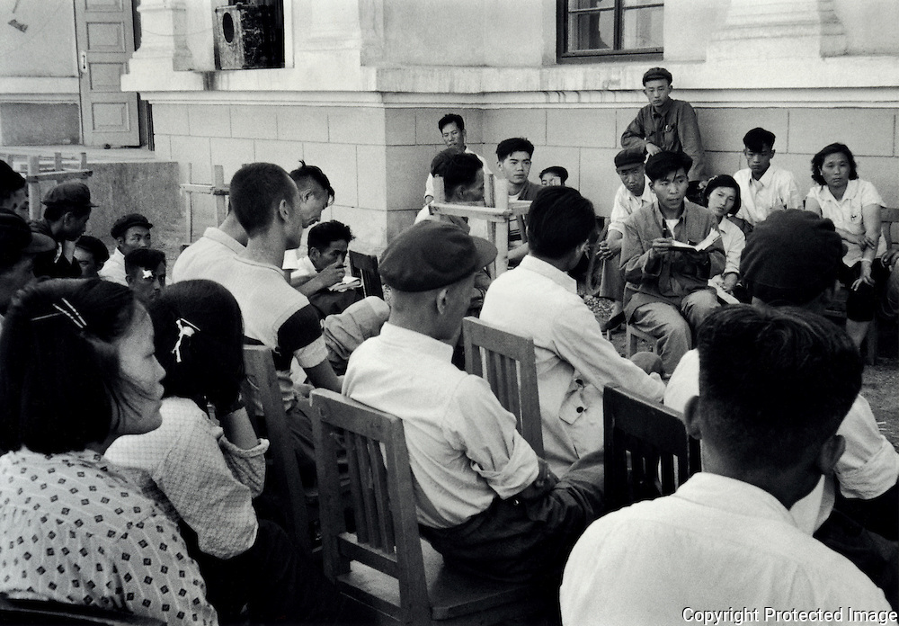 A small group of men, women and children attending an outdoor political meeting in Urumchi, the capital of Xinjiang Province, summer 1956.