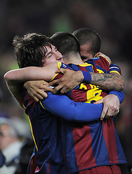 Lionel Messi of Barcelona celebrates with Andreas Iniesta and Dani Alves after scoring his sides opening goal during the UEFA Champions League round of 16 second leg match between Barcelona and Arsenal on March 8, 2011 in Barcelona, Spain.