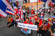 01 FEBRUARY 2014 - BANGKOK, THAILAND: Thai anti-government protestors block a street in Chinatown. The anti-government protest movement, led by the People's Democratic Reform Committee (PDRC) organized a march through the Chinatown district of Bangkok Saturday and disrupted the city's famous Chinese New Year festival. Some streets were blocked and protest leader Suthep Thaugsuban walked through the neighborhood collecting money. Normally the anti-government protestors wear yellow (the color of the King) or anything but red, which is the color worn by the Red Shirts. The march was in advance of massive protests the PDRC has promised for Sunday, Feb. 2 in an effort to block Thais from voting in the national election.     PHOTO BY JACK KURTZ