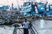 Man with I Love Myanmar t-shirt driving commuter boat at Wholesale Fish Market, Yangon