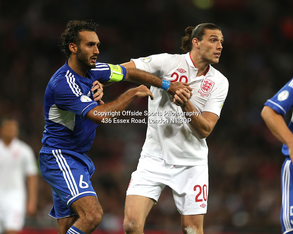 12 October 2012 Football International. England v San Marino.<br /> San Marino captain Alessandro Della Valle holds on to Andy Carroll.