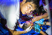 """10 NOVEMBER 2012 - BANGKOK, THAILAND: A Ruamkatanyu Foundation medic looks up while trying to save the life of a boy hit by a vehicle near the Klong Toey slum in Bangkok. The child had severe head injuries and died at the scene. The Ruamkatanyu Foundation was started more than 60 years ago as a charitable organisation that collected the dead and transported them to the nearest facility. Crews sometimes found that the person they had been called to collect wasn't dead, and they were called upon to provide emergency medical care. That's how the foundation medical and rescue service was started. The foundation has 7,000 volunteers nationwide and along with the larger Poh Teck Tung Foundation, is one of the two largest rescue services in the country. The volunteer crews were once dubbed Bangkok's """"Body Snatchers"""" but they do much more than that now.    PHOTO BY JACK KURTZ"""